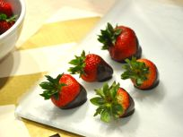 Step Five: Dip strawberries into the chocolate and swirl until partially covered then place on WAX paper!